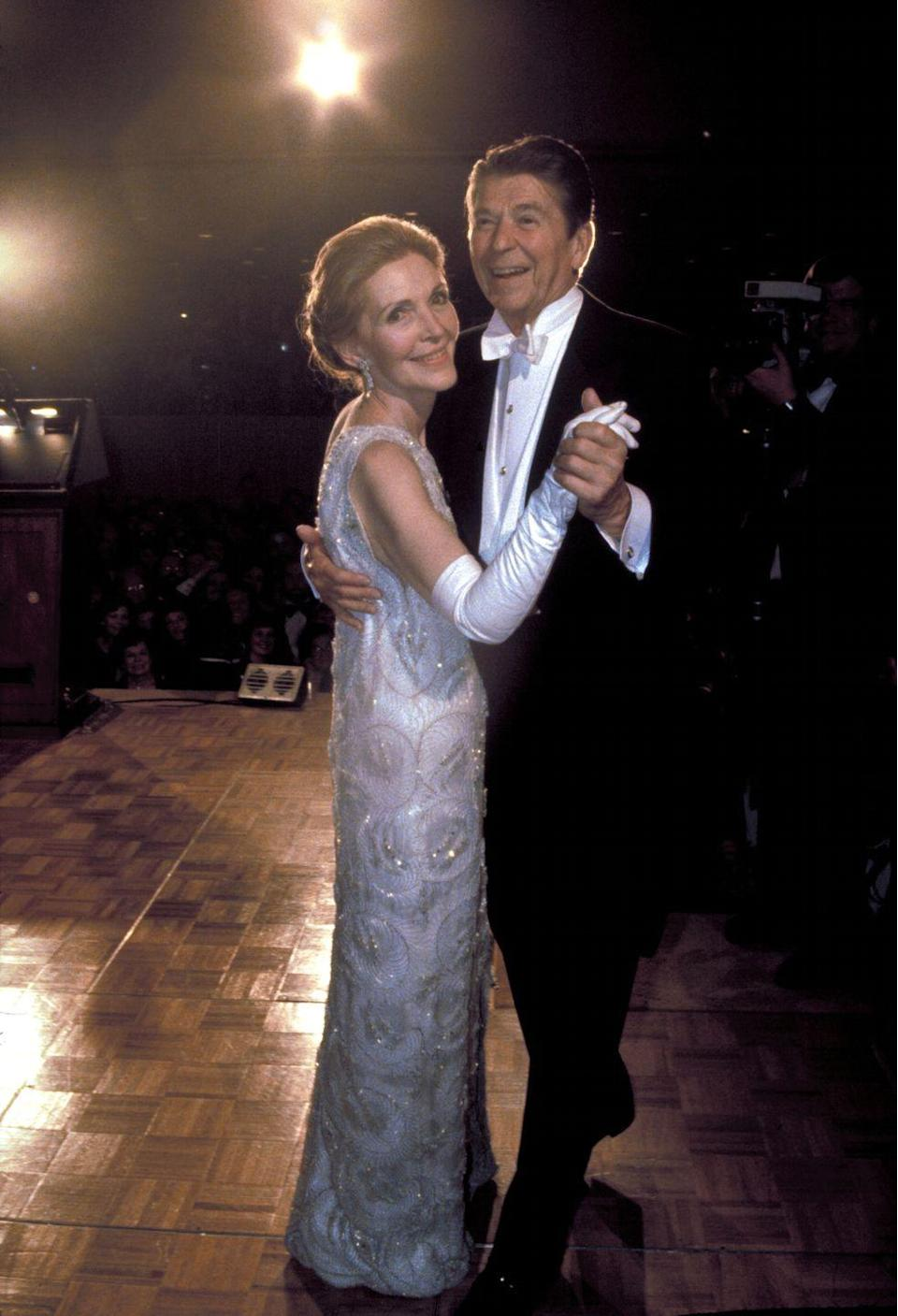 <p>President Reagan shares his first dance with his wife, Nancy Reagan. No stranger to a black tie event, the former Hollywood actress stunned in a white one-shoulder column gown with silver beading, designed by James Galanos.</p>