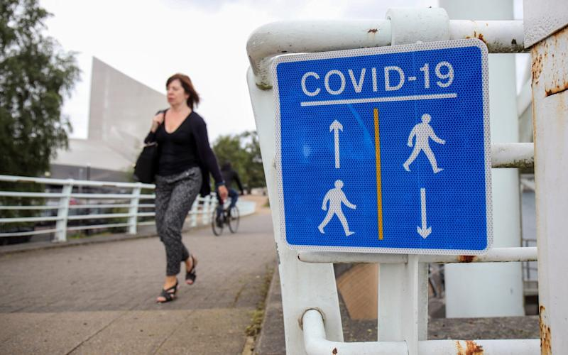 A woman walks past a social distancing sign in Manchester - MOLLY DARLINGTON/REUTERS