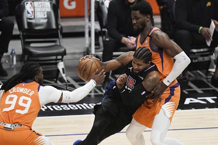 Clippers guard Paul George tries to drive between Phoenix's Jae Crowder and Deandre Ayton.