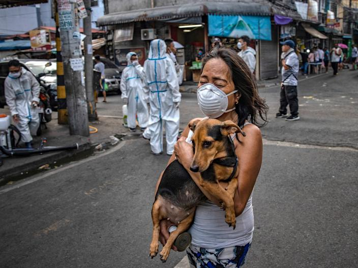 A woman wearing a face mask carries a dog as disinfection workers spray disinfectant along a street at a suburban area on March 23, Metro Manila.