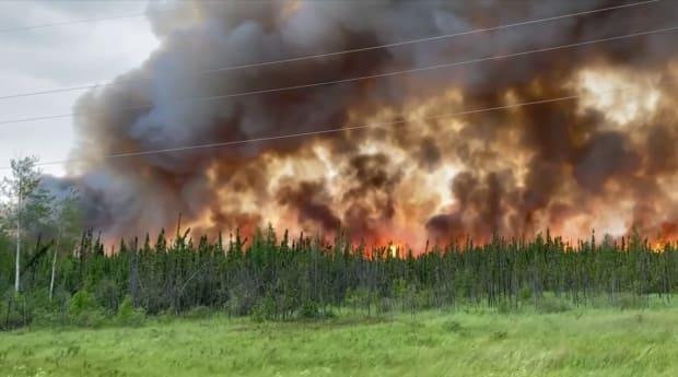 A wildfire burns near Highway 155 north of Buffalo Narrows, Sask. (Marvin Lemaigre/Facebook - image credit)