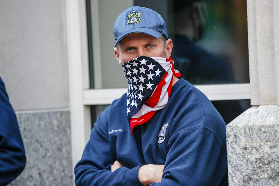 NOVEMBER 06: A cop is seen with the U.S flag mask on as Trump and Biden supporters gathered at the ballot counting center in Philadelphia, Pennsylvania on November 6, 2020. (Photo by Tayfun Coskun/Anadolu Agency via Getty Images)