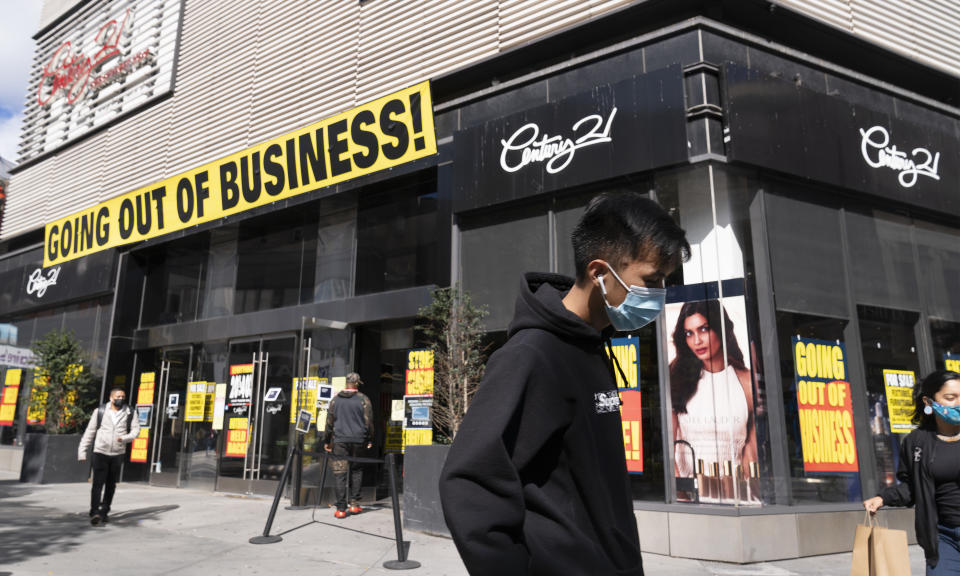 FILE - In this Wednesday, Sept. 30, 2020, file photo, a man wearing a mask amid the coronavirus pandemic walks by a Century 21 department store, in the Brooklyn borough of New York. The discount department store chain has filed for Chapter 11 bankruptcy protection and is closing its 13 stores. Responses to the coronavirus pandemic and police brutality dominated legislative sessions in 2020 and led to many new laws that will take effect in the new year. (AP Photo/Mark Lennihan, File)