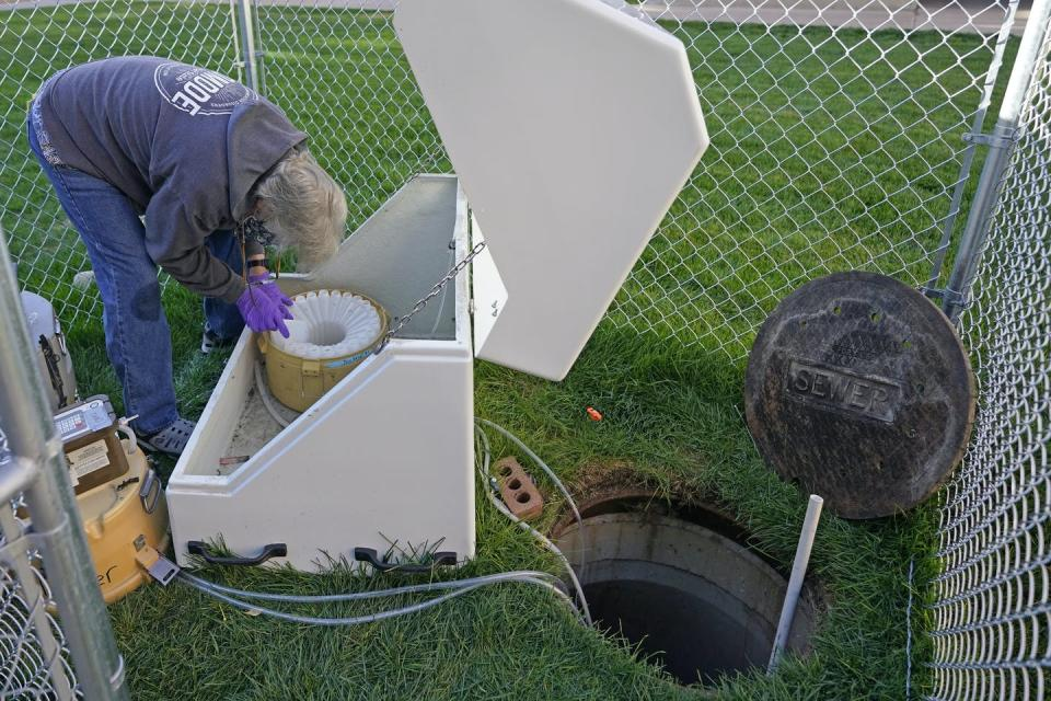 A man bending over a machine with tubes running into an open sewer.