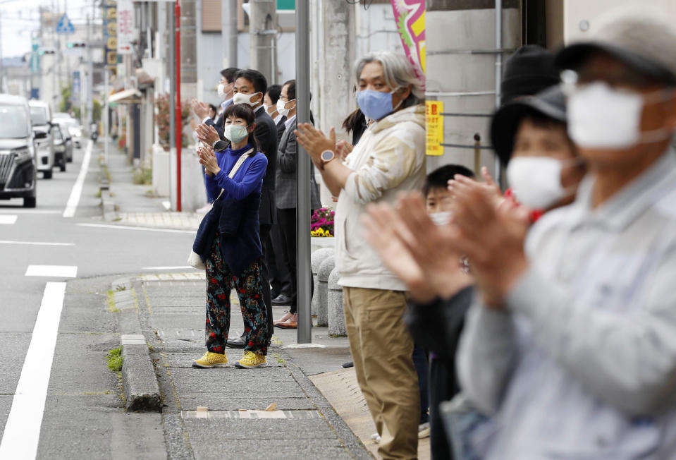 In this May 1, 2020, photo, people clap their hands to show appreciation for medical workers fighting the coronavirus in Susono, Shizuoka Prefecture, central Japan, under a nationwide state of emergency over the virus pandemic. In Japan, the coronavirus has brought not just an epidemic of infections, but also an onslaught of bullying and discrimination against COVID-19 patients, medical workers and others working essential jobs. (Shinji Kita/Kyodo News via AP)