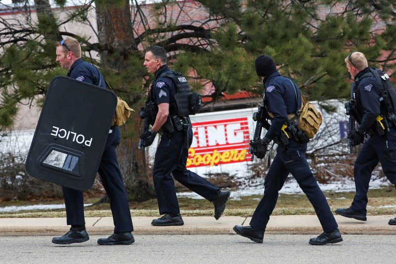 Law enforcement officers stand at the perimeter of a shooting site at King Soopers grocery store in Boulder