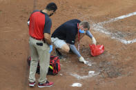 Members of the Reds' crew clean blood out of the dirt from MLB umpire Chris Conroy (98) in the first inning during a baseball game between the Kansas City Royals and the Cincinnati Reds in Cincinnati, Wednesday, Aug. 12, 2020. (AP Photo/Aaron Doster)