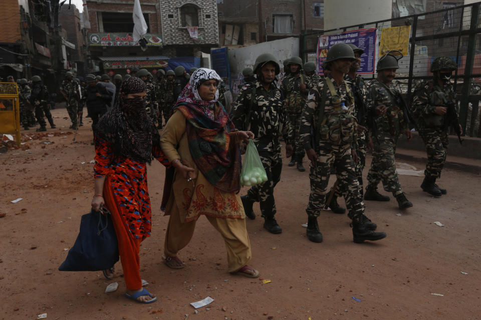 Indian security officers patrol a street in New Delhi, India, Wednesday, Feb. 26, 2020. At least 20 people were killed in three days of clashes in New Delhi, with the death toll expected to rise as hospitals were overflowed with dozens of injured people, authorities said Wednesday. The clashes between Hindu mobs and Muslims protesting a contentious new citizenship law that fast-tracks naturalization for foreign-born religious minorities of all major faiths in South Asia except Islam escalated Tuesday. (AP Photo/Rajesh Kumar Singh)