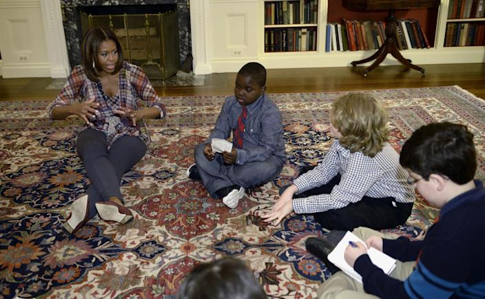 """First lady Michelle Obama sits on the floor with """"kid reporters,"""" from second from left, Justin Creppy, 6, from Upper Marlboro, Md., Zachary Shannon, 10, from Garrison, N.Y., and Raphael Chambers, 13, from Reston, Va., right, Monday, April 21, 2014, in the Library of the White House in Washington. (AP Photo/Susan Walsh)"""