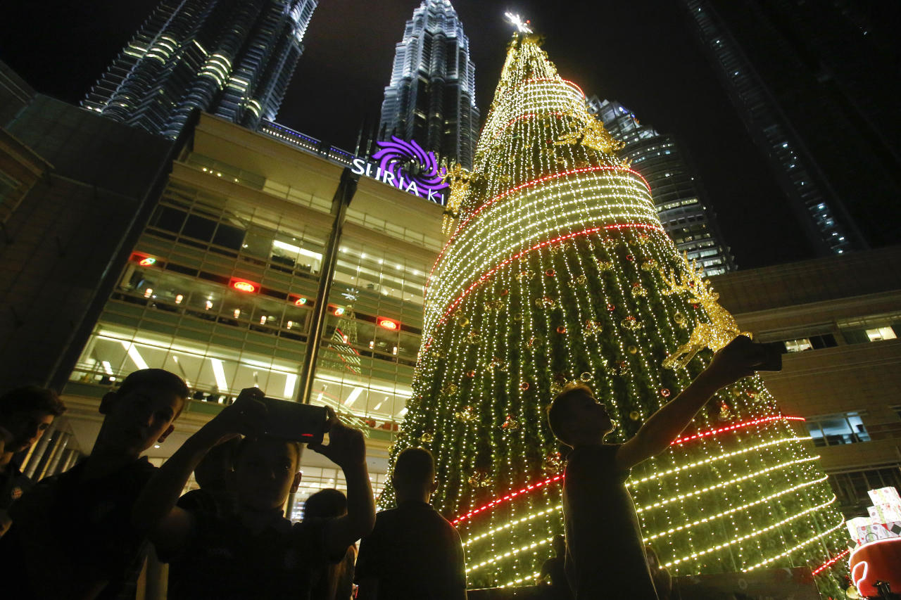 Tourists take selfies in front of a Christmas tree at the Petronas Twin Towers in Kuala Lumpur, Malaysia, Wednesday, Dec. 13, 2017. Shopping malls in the Muslim-dominated nation have been decorated with Christmas trees, Santa Claus figures and illuminations to attract year-end shoppers. (AP Photo/Sadiq Asyraf)