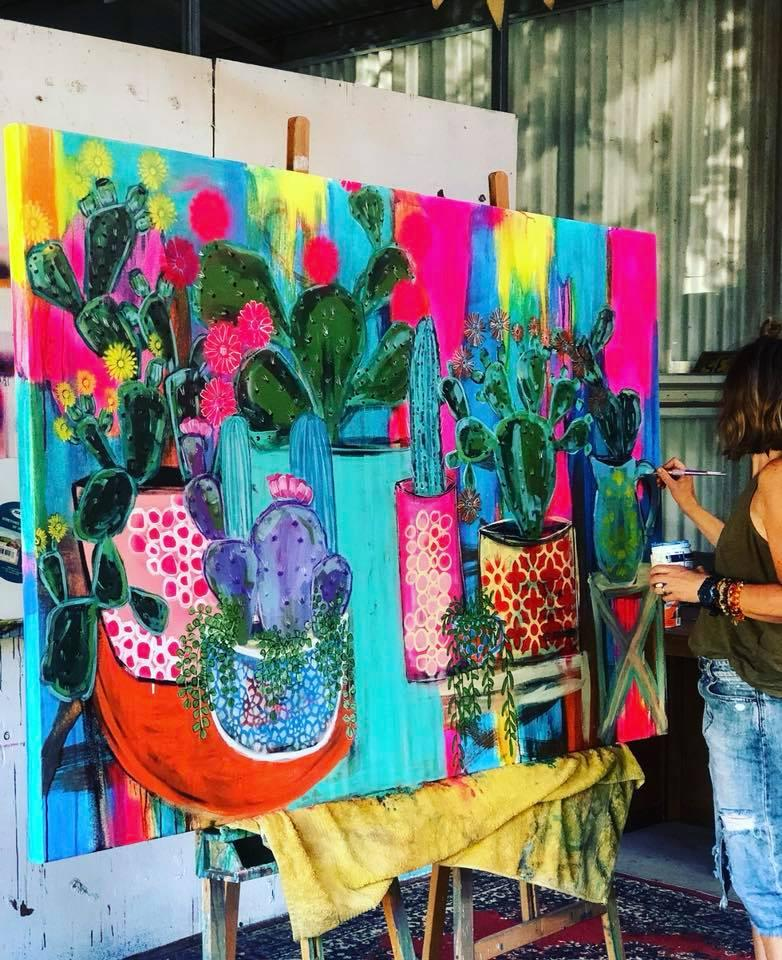 A large canvas painting of cacti in bright primary colours in worked on by Jacinta Haycock