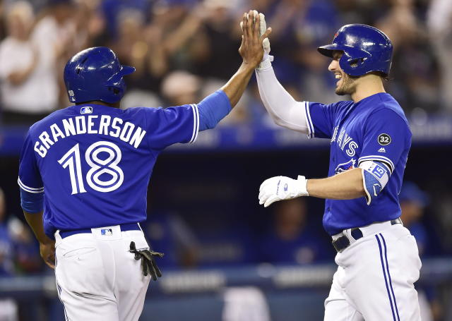 Toronto Blue Jays' Randal Grichuk, right, celebrates his two-run home run against the Baltimore Orioles with teammate Curtis Granderson during eighth-inning baseball game action in Toronto, Sunday, July 22, 2018. (Frank Gunn/The Canadian Press via AP)