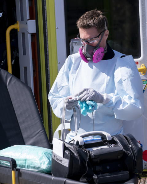 A paramedic cleans ambulance equipment after transporting a patient to the Verdun Hospital in Montreal, on Monday, April 6, 2020. Prime Minister Justin Trudeau says he's confident Canada will still be able to import N95 protective masks form the U.S. despite an export ban and says he will talk to U.S. President Donald Trump in the coming days. (Paul Chiasson/The Canadian Press via AP)