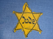 FILE - In this Wednesday, Jan. 22, 2014 file photo, the Yellow Star badge of Heinz-Joachim Aris (Dresden 1941) reading 'Jew' is displayed in a showcase during a press preview in the new special exhibition 'Shoes of the Dead - Dresden and the Shoah' at the Military History Museum in Dresden, Germany. Before local anti-Jewish laws were enacted, before neighborhood shops and synagogues were destroyed, and before Jews were forced into ghettos, cattle cars, and camps, words were used to stoke the fire of hate. 'ItStartedWithWords' is a digital, Holocaust education campaign posting weekly videos of survivors from across the world reflecting on those moments that led up to the Holocaust. (AP Photo/Jens Meyer, file)