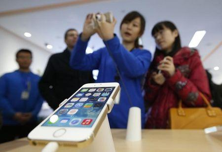 A staff of a China Mobile shop explains a function of the iPhone 5s to a customer in Beijing