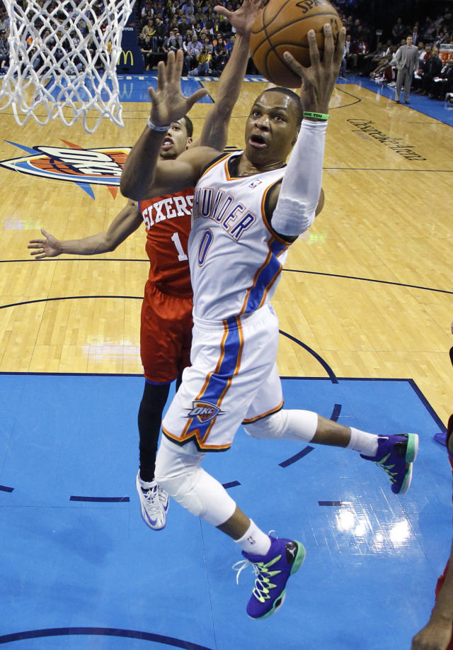 Oklahoma City Thunder guard Russell Westbrook (0) goes up for a shot in front of Philadelphia 76ers guard Michael Carter-Williams (1) during the second quarter of an NBA basketball game in Oklahoma City, Tuesday, March 4, 2014. Oklahoma City won 125-92. (AP Photo/Sue Ogrocki)