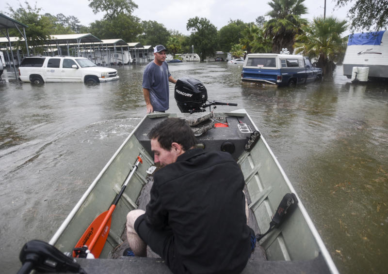 Levi Kelley sits in Clint Tucker's boat after he was rescued by Tucker, who is a member of the Cajun Navy, after water trapped him in his his trailer, Thursday, Sept. 19, 2019, in Vidor, Texas, following flooding from Tropical Depression Imelda. (Ryan Welch/The Beaumont Enterprise via AP)