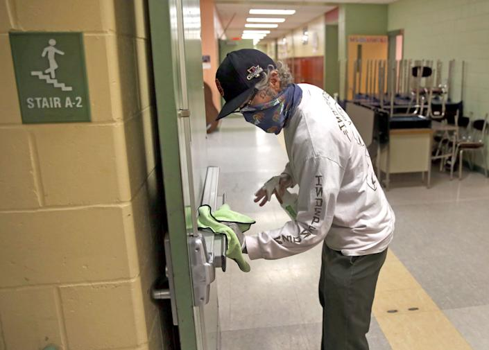 A custodian wipes down a hallway doorway at the Mildred Avenue K-8 School building in Boston ahead of the school reopening last week. School systems are taking many measure to keep students safe during the pandemic, including placing social distancing markers on the floors and increasing hand sanitizer stations. (Photo: Photo by David L. Ryan/The Boston Globe via Getty Images)