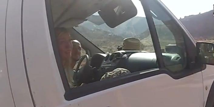 A still from police bodycam footage showing Gabby Petito and Brian Laundrie inside a white van, looking out.