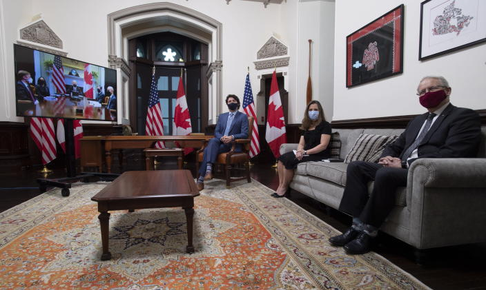 Canadian Prime Minister Justin Trudeau is seen with Deputy Prime Minister and Minister of Finance Chrystia Freeland and Foreign Affairs Minister Marc Garneau as they meet virtually with United States President Joe Biden from his office on Parliament Hill in Ottawa, Ontario, Tuesday, Feb. 23, 2021. (Adrian Wyld/The Canadian Press via AP)