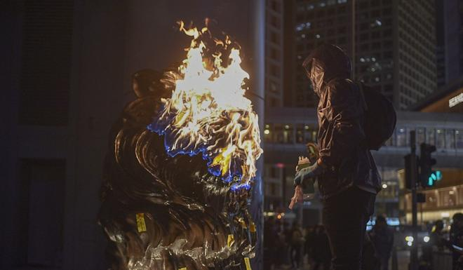 An anti-government protester sets fire to one of the lion statues outside HSBC's headquarters on New Year's Day. Photo: AFP