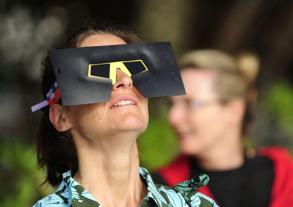 A spectator views the solar eclipse through special eclipse viewing glasses.