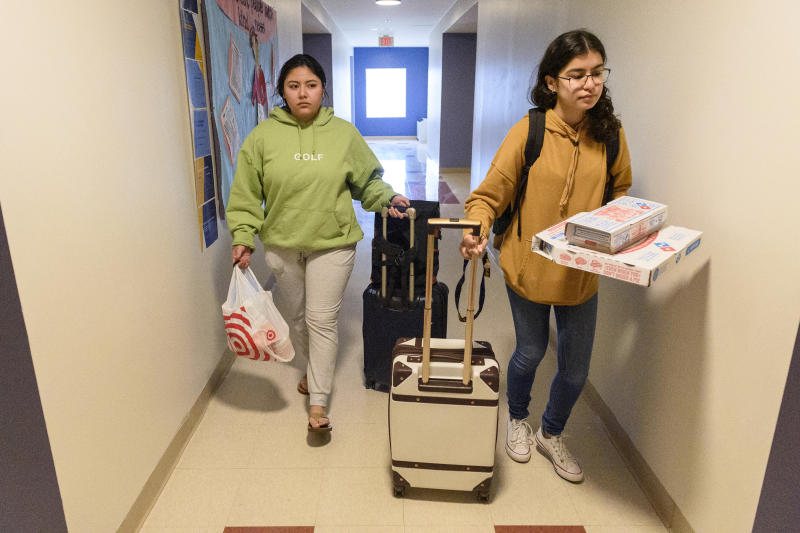 University of New Haven students Victoria Salazar and Alexis Cervantes (from left) leave their nearly deserted residence hall room with bags packed after the campus closed due to coronavirus concerns on March 11, 2020. California natives, the two planned to live in a hotel until a flight they booked for their spring break will bring them home. (Mark Mirko/Hartford Courant/Tribune News Service via Getty Images)