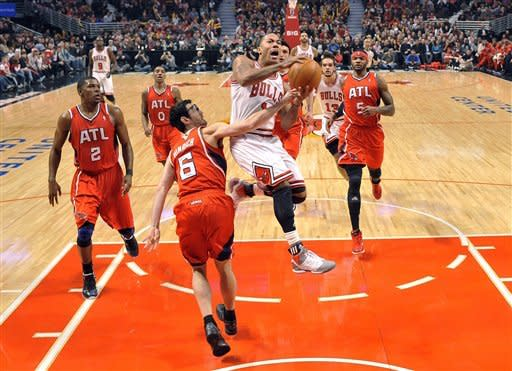 Chicago Bulls guard Derrick Rose, center, drives to the basket as Atlanta Hawks guard Kirk Hinrich (6) defends during the first quarter of an NBA basketball game, Monday, Feb. 20, 2012, in Chicago. (AP Photo/Brian Kersey)