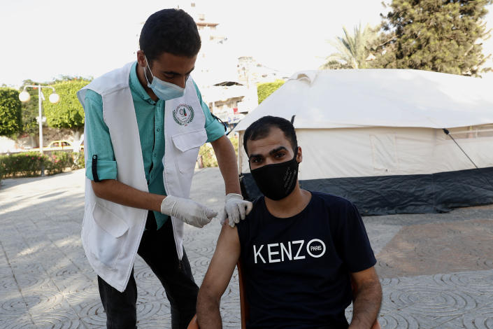 A nurse gives a shot of the Pfizer COVID-19 vaccine to a youth at a temporary clinic tents at the Unknown soldier square in Gaza City, in Gaza City, Thursday, Sept. 23, 2021. (AP Photo/Adel Hana)