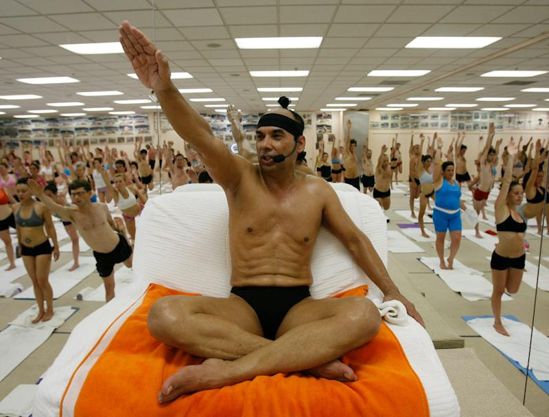 Bikram Choudhury (who goes by Bikram), seen here in 2006, has a chair at the front of his hot yoga class, which is filled with hundreds of students.