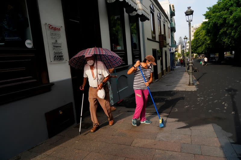 A man walks with an umbrella as women clean the ash from the street following the eruption of a volcano on the Canary Island of La Palma