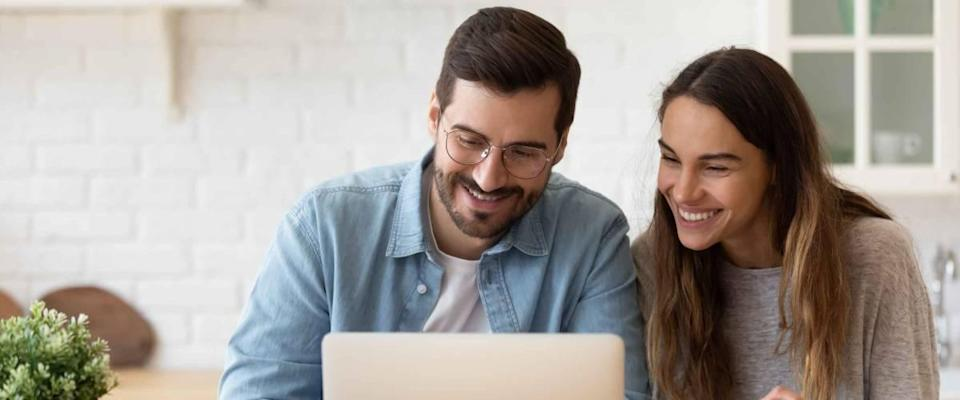 Young couple sitting at kitchen table, smiling, looking at laptop