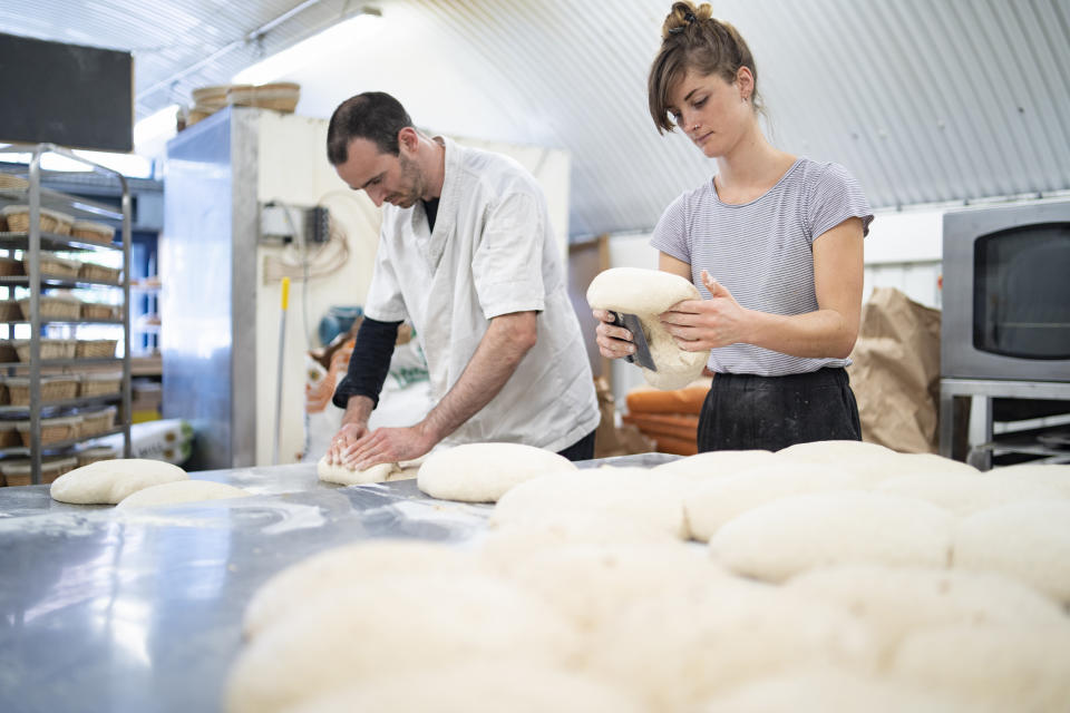 Man and woman preparing loaves of bread in bakery