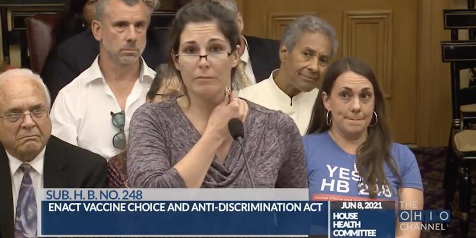 A nurse at the Ohio Statehouse hearing holding a key to her neck while the audience looks skeptically on.