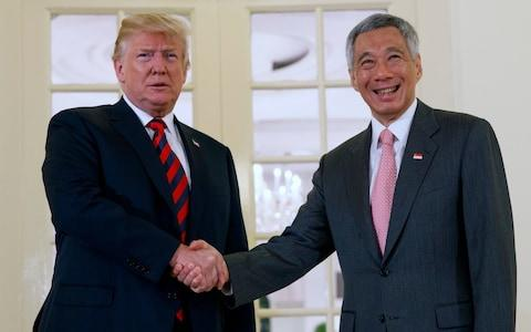 President Donald Trump shakes hands as he meets with Singapore Prime Minister Lee Hsien Loong ahead of a summit with North Korean leader Kim Jong-un - Credit: AP