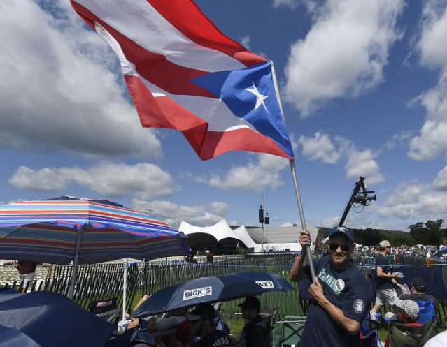 Miguel Rosario of Atlantic City, N.J., waves a Puerto Rican Flag while waiting for the start of the National Baseball Hall Of Fame induction ceremony at the Clark Sports Center on Sunday, July 21, 2019, in Cooperstown, N.Y. (AP Photo/Hans Pennink)
