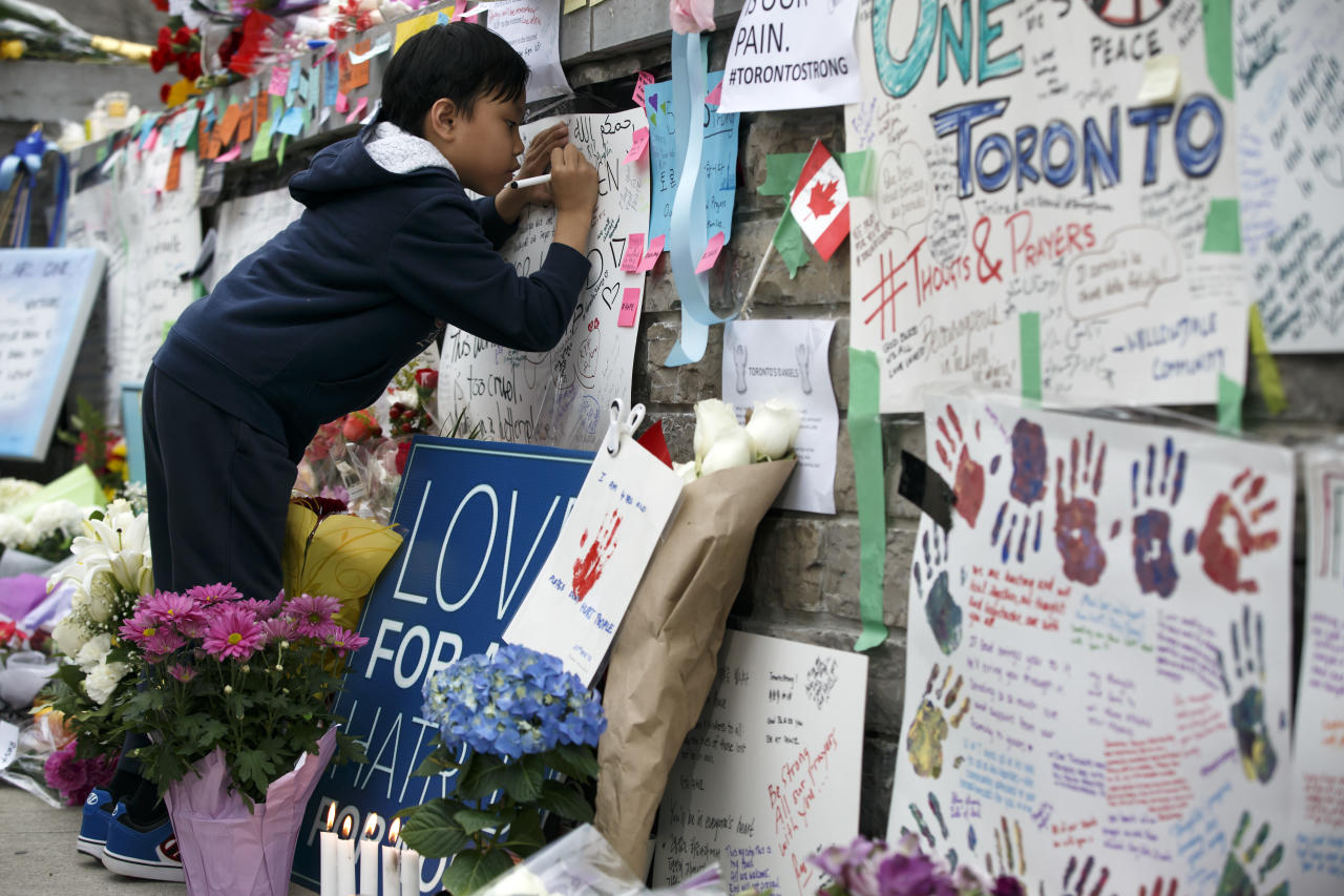 <p>A young boy writes a message at a memorial for victims of the mass killing on Yonge Street in Toronto. Cole Burston/Getty Images </p>