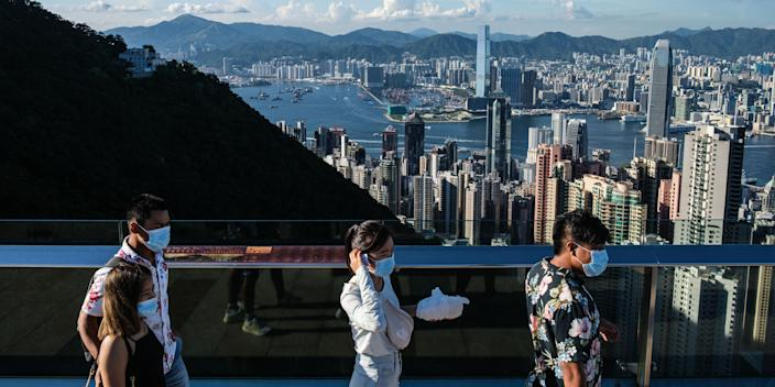 Visitors walk along a viewing platform on Victoria Peak in Hong Kong on July 28, 2020. (Photo by ANTHONY WALLACE / AFP) (Photo by ANTHONY WALLACE/AFP via Getty Images)