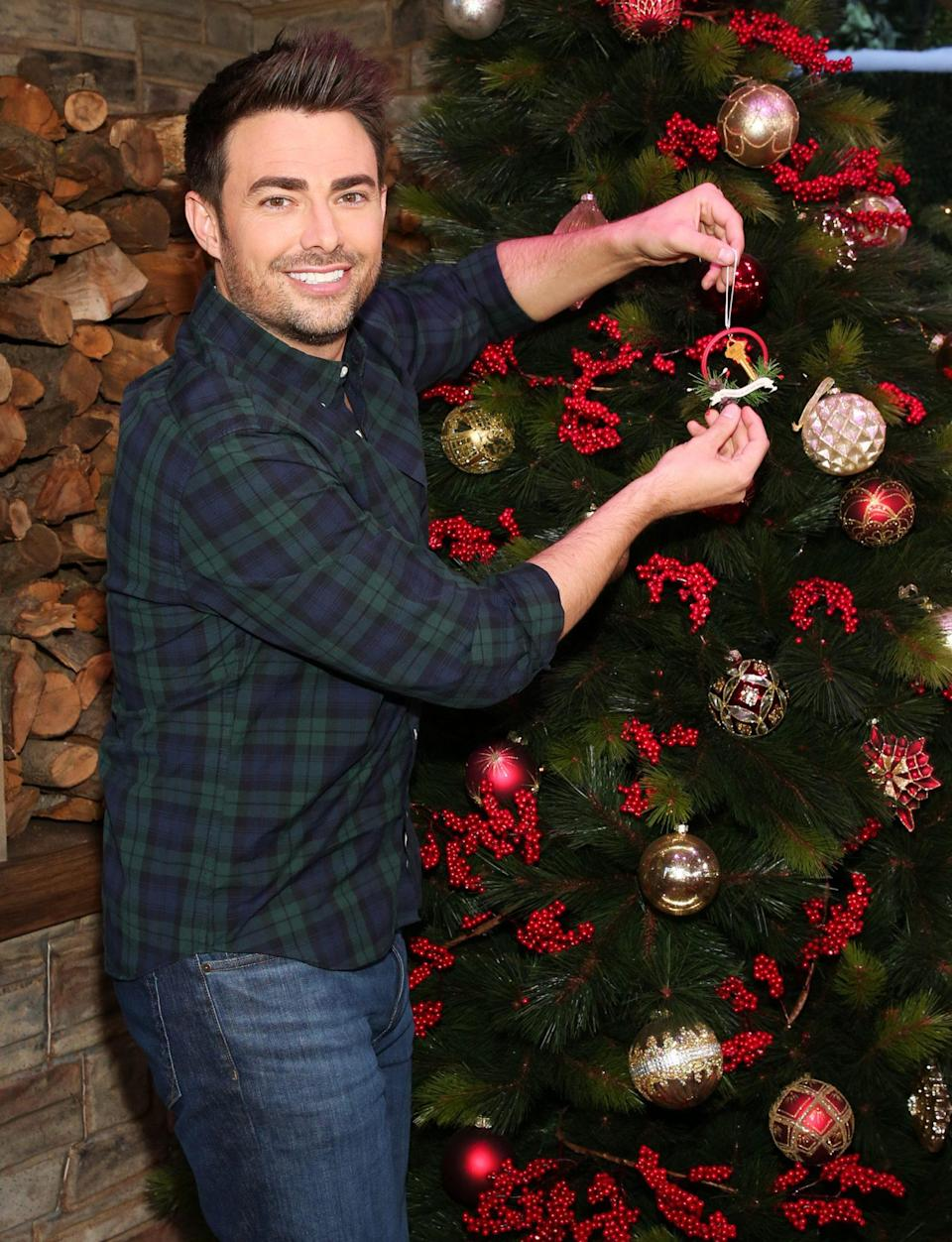 <p>Jonathan Bennett hangs an ornament on the Christmas tree during a visit to Hallmark Channel's <i>Home & Family </i>on Tuesday in Universal City, California. </p>