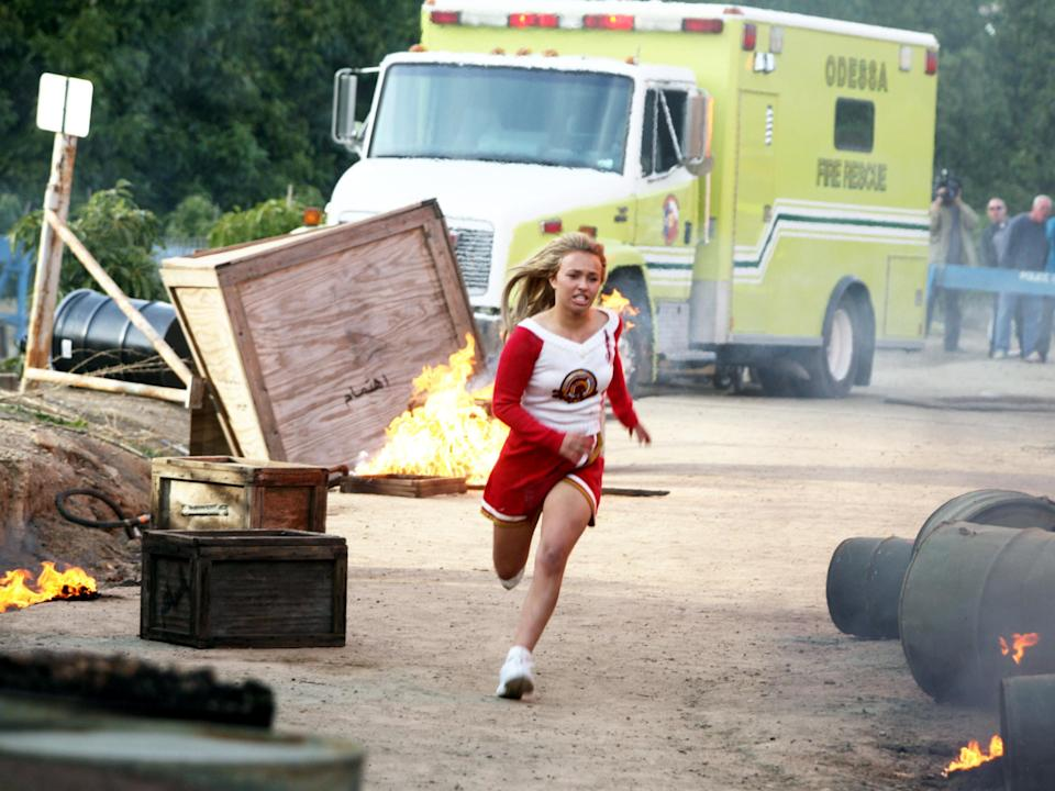 Hayden Panettiere runs away from an ambulance in a cheerleader outfit