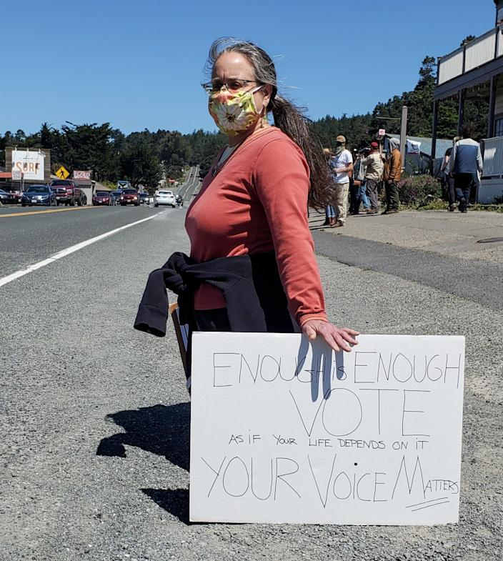 Lisa Joakimides takes a knee with her homemade sign during a George Floyd protest along Highway 1 in Gualala, Calif.