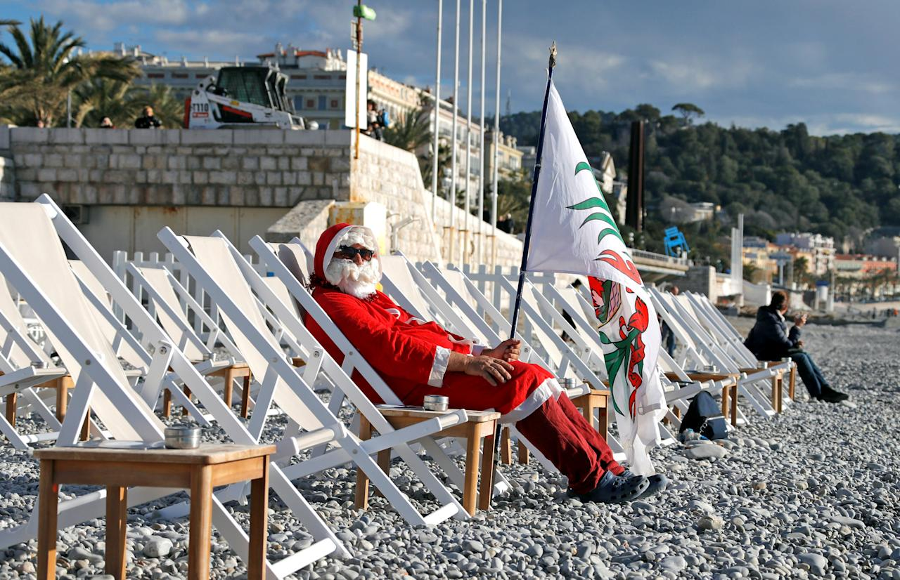 A man dressed as Santa Claus sits on the beach as he waits to take part in the traditional Christmas season swim in Nice, France, December 17, 2017.        REUTERS/Eric Gaillard