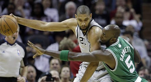San Antonio Spurs' Tim Duncan (21) is pressured by Boston Celtics' Kevin Garnett (5) during the first quarter of an NBA basketball game, Saturday, Dec. 15, 2012, in San Antonio. (AP Photo/Eric Gay)