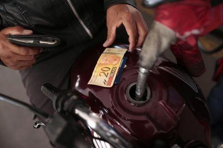 A gas station employee refuels a motorcycle in Brasilia