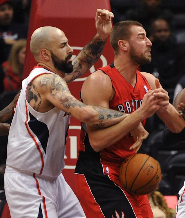 Atlanta Hawks' Pero Antic, left, steals the rebound from Toronto Raptors' Jonas Valanciunas in the first half of their NBA basketball game Tuesday, March 18, 2014, in Atlanta. (AP Photo/David Tulis)