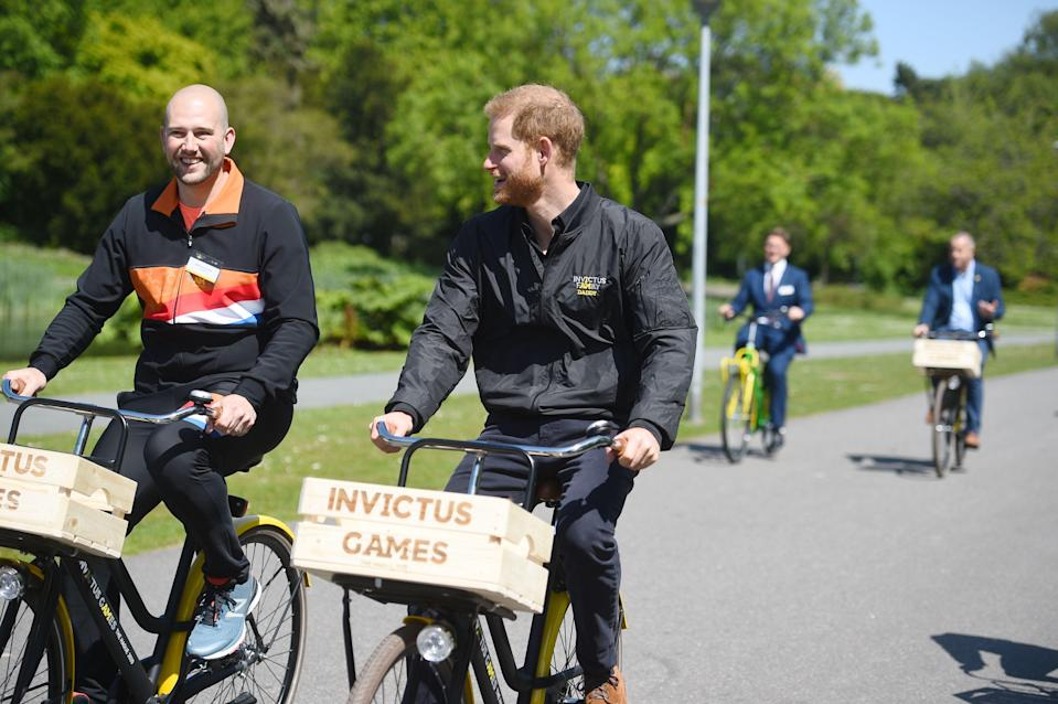 The Duke of Sussex (centre) rides a bicycle in The Hague [Photo: PA]