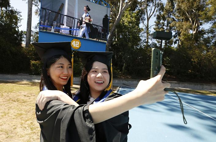 Yuying Wang, left, takes a selfie with Ziyan Wu as graduating UCLA students.