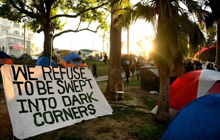 Los Angeles, CA March 24, 2021-A sign is placed between homeless tents during a rally at Echo Park on Wednesday. Homeless advocates held a rally to prevent the closure of LA's largest self-owned homeless park.  (Wally Skalij / Los Angeles Times)