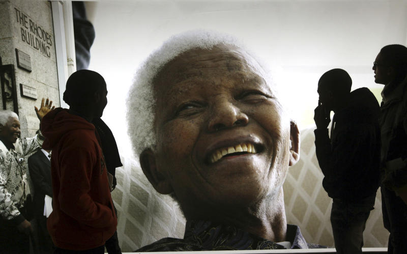 """FILE - In this June 27, 2013 file photo, giant photographs of former South African President Nelson Mandela are displayed at the Nelson Mandela Legacy Exhibition at the Civic Centre in Cape Town, South Africa. The ailing former president is not """"doing well"""" but is continuing to put up a courageous fight from his """"deathbed,"""" members of his family have told the South African Broadcasting Corporation in an interview. (AP Photo/File)"""
