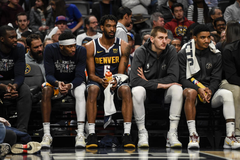 Members of the Denver Nuggets sitting on the bench.